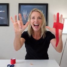Hand Therapist demonstrates her right middle finger triggering and left hand has tape applied to middle finger used to stop trigger finger.