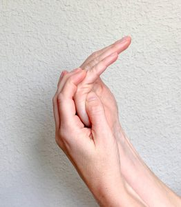 Image is using other hand to stretch small finger MP joint into flexion